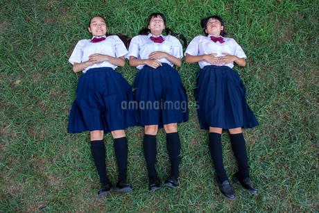 原っぱに寝転がる中学生の写真素材 [FYI01761187]