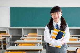 教室でノートを抱える女子中学生の写真素材 [FYI01761235]