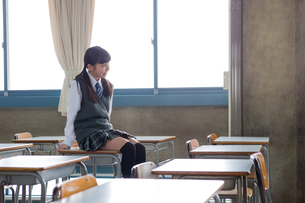 教室で机に座る女子中学生の写真素材 [FYI01761266]