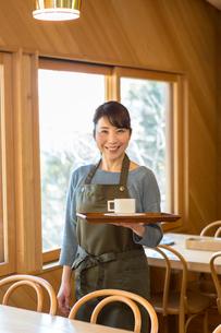 コーヒーを乗せたトレーを持って立つ女性店員の写真素材 [FYI01761341]