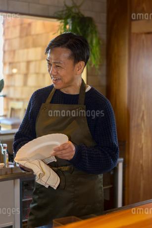 カウンターで皿を拭く男性の写真素材 [FYI01761468]