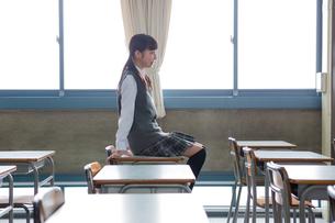 教室で机に座る女子中学生の写真素材 [FYI01761475]