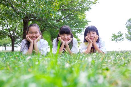 草の上にうつぶせで頬杖をつく中学生の写真素材 [FYI01761491]