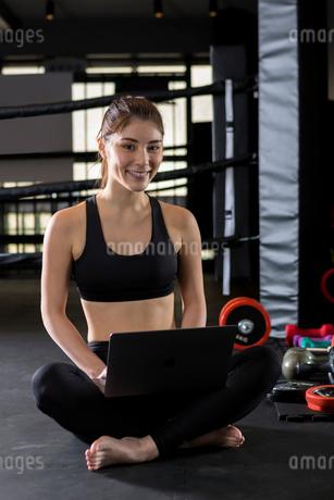 ジムでパソコンを使用する女性の写真素材 [FYI01761548]