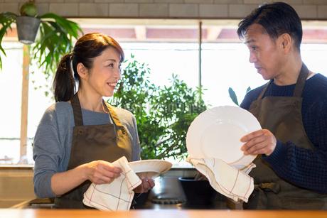 カウンターで皿を拭く夫婦の写真素材 [FYI01761614]