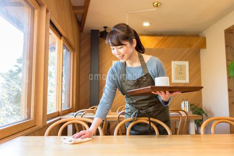 テーブルの片付けをする女性店員の写真素材 [FYI01761682]