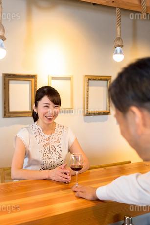 女性客に赤ワインを出す男性店員の写真素材 [FYI01761789]