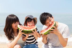 浜辺でスカイを食べる家族の写真素材 [FYI01761814]
