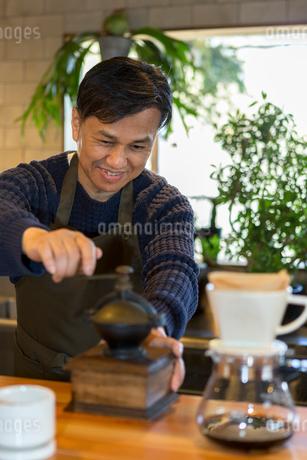 コーヒー豆を挽く男性の写真素材 [FYI01761847]