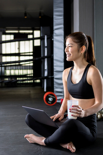 ジムでパソコンを使用する女性の写真素材 [FYI01761862]
