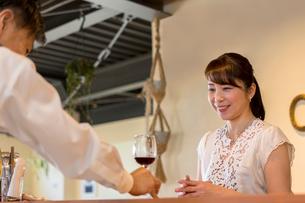 女性客に赤ワインを出す男性店員の写真素材 [FYI01761879]