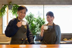 カフェのカウンターに立つ夫婦の写真素材 [FYI01761965]