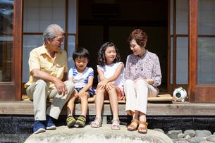 縁側に座る老夫婦と孫の写真素材 [FYI01762140]
