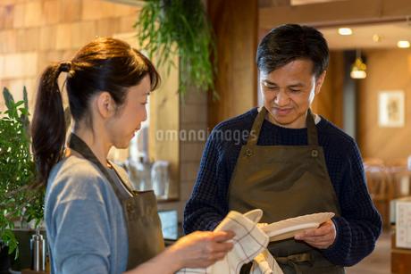 カウンターで皿を拭く夫婦の写真素材 [FYI01762185]
