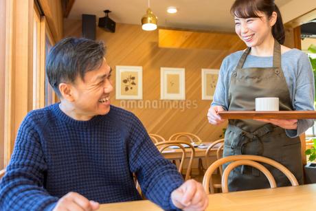 コーヒーを提供する女性店員と男性客の写真素材 [FYI01762662]