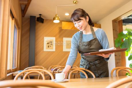 テーブルの片付けをする女性店員の写真素材 [FYI01762706]