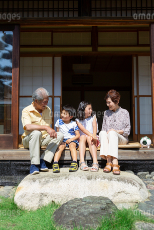 縁側に座る老夫婦と孫の写真素材 [FYI01763155]