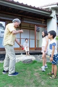 孫にけん玉を披露する祖父と見まもる祖母の写真素材 [FYI01763842]