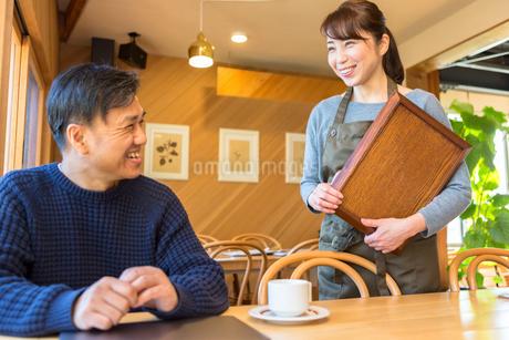 コーヒーを提供する女性店員と男性客の写真素材 [FYI01764172]