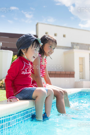 プールサイドに座る姉弟の写真素材 [FYI01764200]