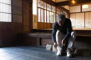 玄関で靴紐を結ぶシニア男性の写真素材 [FYI01764220]