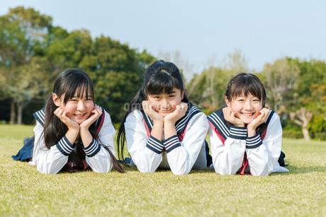 芝生に寝転んで頬杖をつく女子中学生の写真素材 [FYI01764250]