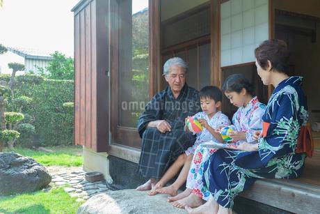 縁側でスイカを食べる祖父母と孫の写真素材 [FYI01764270]
