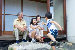 けん玉をする男の子と見守る祖父母と姉の写真素材 [FYI01764296]