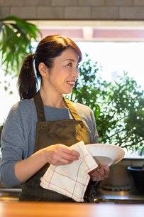 カウンターで皿を拭く女性の写真素材 [FYI01764383]