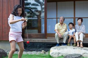 けん玉をする女の子と見守る祖父母と弟の写真素材 [FYI01764386]
