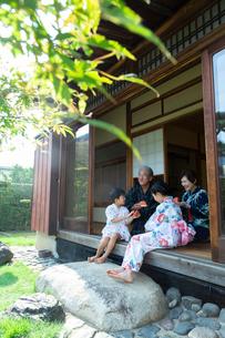 縁側でスイカを食べる祖父母と孫の写真素材 [FYI01764412]