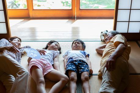 和室で昼寝をする祖父母と孫の写真素材 [FYI01764444]