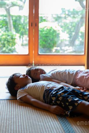 和室で昼寝する姉弟の写真素材 [FYI01764478]