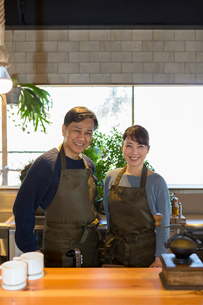 カフェのカウンターに立つ夫婦の写真素材 [FYI01764510]