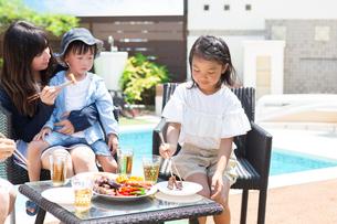プールサイドで食事をする家族の写真素材 [FYI01764604]