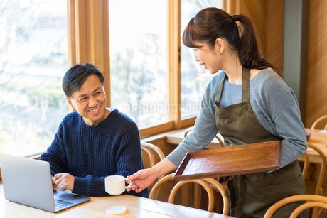 コーヒーを提供する女性店員と男性客の写真素材 [FYI01764627]
