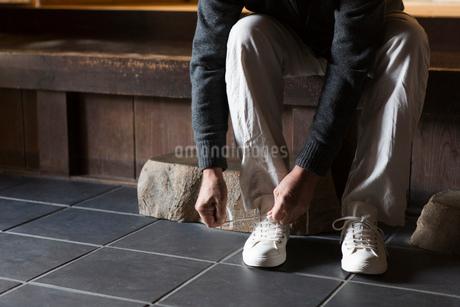 玄関で靴紐を結ぶシニア男性の写真素材 [FYI01764708]