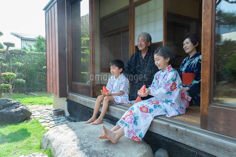 縁側に座る祖父母と孫の写真素材 [FYI01764723]