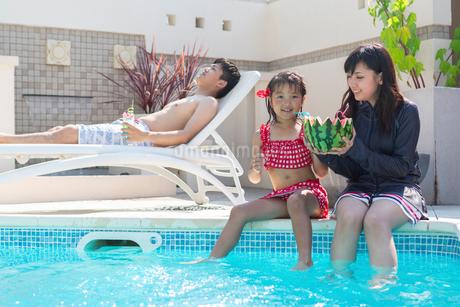 プールサイドに座る家族の写真素材 [FYI01764743]