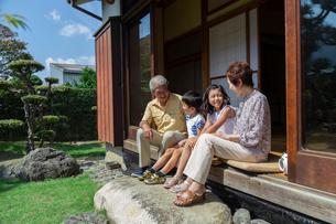 縁側に座る老夫婦と孫の写真素材 [FYI01764812]
