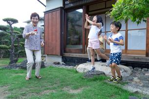 孫にけん玉を披露する祖母の写真素材 [FYI01764858]