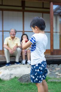けん玉をする男の子と見守る祖父と姉の写真素材 [FYI01764863]