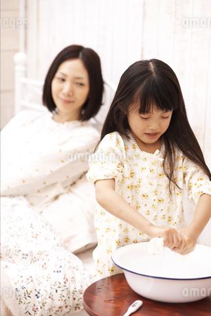 タオルを絞る女の子と病気の母親の写真素材 [FYI01767042]
