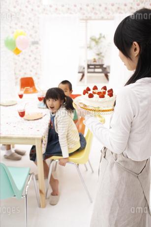 ケーキを運ぶ母親と待つ子供の写真素材 [FYI01767158]