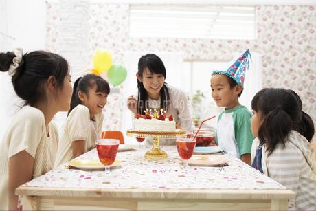 ケーキのろうそくを消す男の子の写真素材 [FYI01767163]