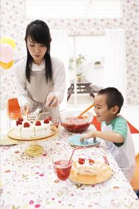 ケーキを取り分ける母と待つ子供の写真素材 [FYI01767191]