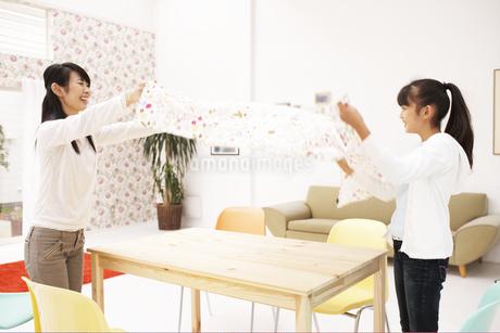 テーブルクロスを広げる母と子供の写真素材 [FYI01767273]