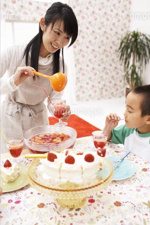 ジュースをつぐ母親と男の子の写真素材 [FYI01767500]