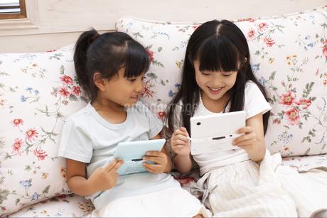 ソファでゲームをして遊ぶ女の子の写真素材 [FYI01767579]