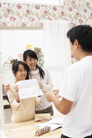 父親にテストを見せる女の子と母の写真素材 [FYI01767790]